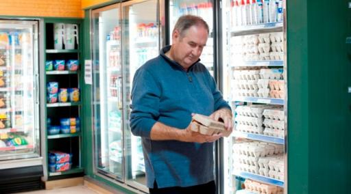 Man holding in store holding carton of eggs
