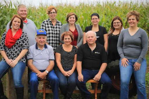 a group of farmers standing in front of a corn field