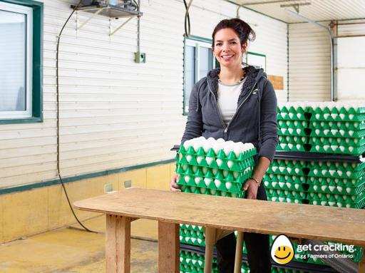 woman holding multiple cartons of freshly laid eggs
